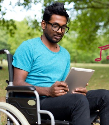Man in a wheelchair using an iPad