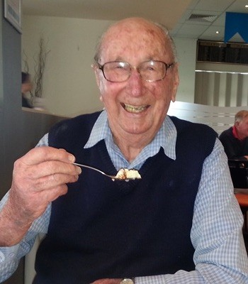 Elderly man eating at a table